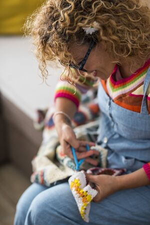 Artistic creative caucasian woman at home doing artwork and artcraft handmade - indoor leisure activity with textile fabric and colors - joyful lifestyle people 写真素材