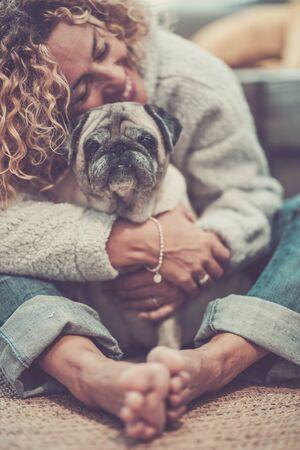 Love and friendship concept with happy defocused caucasian adult woman hug her lovely old dog pug - animal therapy and best friend together forever