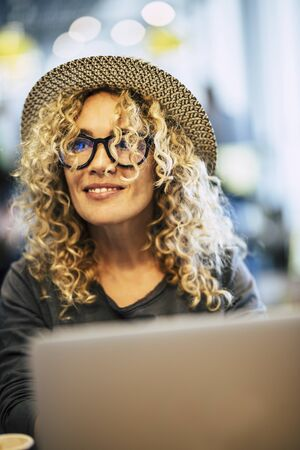 Beautiful adult cheerful happy woman work with laptop computer and bokeh coloured background - concept of technology and nice people with smart modern job - eyeglasses and blonde curly hair 写真素材