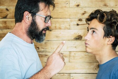Adult caucasian man father telling out her teenager son at home - family portrait and education concept - generations and parentship - wooden background