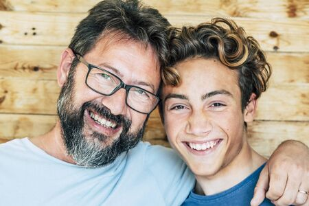 Cheerful people portrait with father and son hug and laughing a lot together having fun and looking at the camera - wooden background and joyful generations concept-handsome young and old males