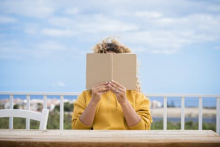 Unrecognizable woman read a paper book outdoor with wooden table in front of her and blue beautiful sky in background - concept of reading and studying for people 写真素材