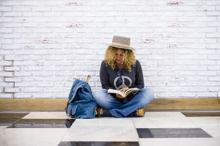 Alternative trendy travel people lifestyle beautiful curly fashion adult woman sit down on the floor and read a booko with her blue backpack nera her - white bricks background 写真素材