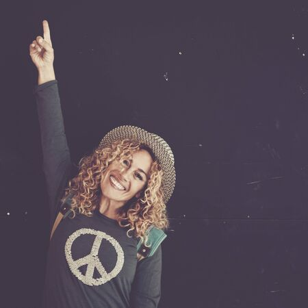 Cheerful beautiful caucasian adult woman with blonde curly hair and trendy hat sign with finger and smile at the camera for sale or offer message - black wall in background and peace on the shirt