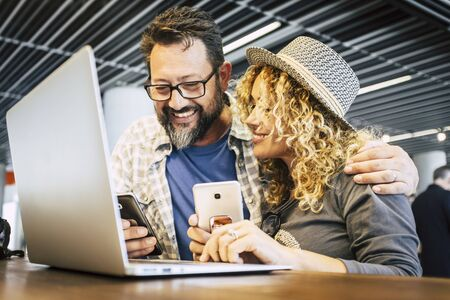 Smart working and digital nomad. alternative eveywhere office concept with couple of caucasian people use phones device and laptop computer during fly travel in airport or bar 写真素材