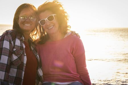 two cacuasian females friends at the beach with sunlasses sitting and posing hugged to the photo - beautiful sunset on the background - womans hugged and similing and looking at the camera