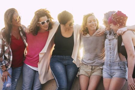Group of adult and young caucasian friends enjoy together in friendship without social distance in freedom - beautiful mixed generations women have fun together outdoor 写真素材