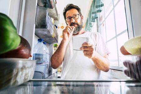 Adult caucasian man taking note list of food looking inside the open fridge at home - kitchen activity and alternative point of view - market shopping and quarantine lockdown stayhome coronavirus time 写真素材