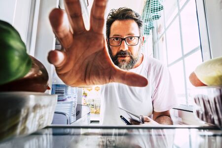 Adult caucasian man take healthy food from an open fridge - closeup inside view - weight loss concept -  home activity in the kitchen - quarantine coronavirus people concept stay home