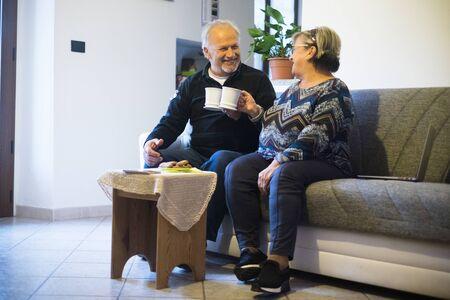 Nice cheerful couple of caucasian senior people drink tea or coffee at home enjoying indoor activity during coronavirus quarantine lockdown emergency