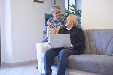 Retired senior people at home enjoying and use technology laptop computer during coronavirus lockdown quarantine time - elderly lifestyle with internet connection 写真素材