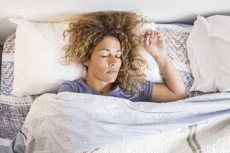 Beautiful caucasian adult woman sleep and relax at home in the bed - concept of early morning activity before wake up and go work - concept of quarantine lockdown 写真素材