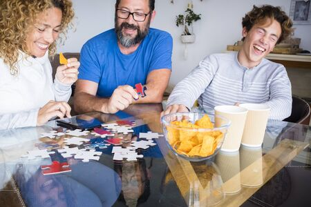 Caucasian family play together on the table at home and have fun laughing a lot - indoor leisure activity and playful time during coronavirus quarantine 写真素材
