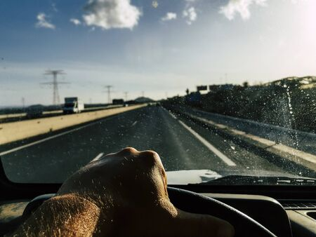 Car driving concept with close up of adult caucasian male hands and roads in background outside the dirty window - concept of man drive the vehicle for transport or vacation
