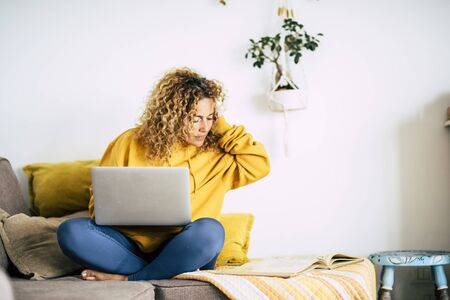Adult blonde woman at home work with computer laptop and internet connection -concept of technology activity and smart job with modern people - lockdown quarantine for covid-19