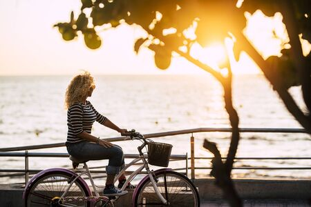 Inependent free woman enjoying the outdoor leisure activity riding a bike with sunset and ocean in background - concept of nice free lifestyle and vacation for lonely ladies 写真素材