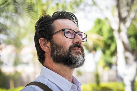 Handsome adult mature man with eyeglasses look and think in a portrait with green defocused background - professional people concept with trendy eyewear and beard
