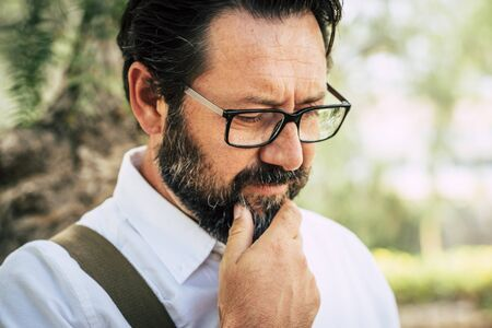 Worried adult caucasian 50 years old man touch the beard and think alone - eyeglasses and people outdoor with green park defocused background