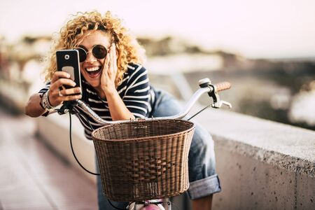 Cheerful happy beautiful curly trendy woman taking selfie picture with modern phone - people enjoying the outdoor technology leisure activity -   defocused beautiful background 写真素材