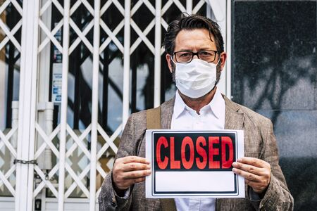 Adult professional businessman with closed sign outside his store for coronavirus economy crisis emergency for lockdown at home - business recession concept with owner outdoor shop