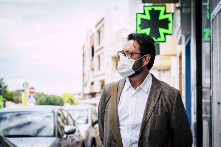 Adult mature caucasian man walk outdoor in the city using healthy protection mask for virus contagion and pharmacy in background - coronavirus new lifestyle concept