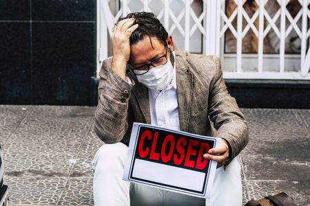Sad and desperate business man sit down outside his closed store for coronavirus lockdown economy business crisis - people with mask protection for virus and unemployed concept Stockfoto
