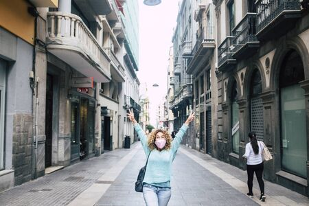 Happy adult woman in the middle of the commercial store street in the city give up arms for end of coronavirus covid-19 virus emergency and back to free life for people - emergency phases concept Stockfoto