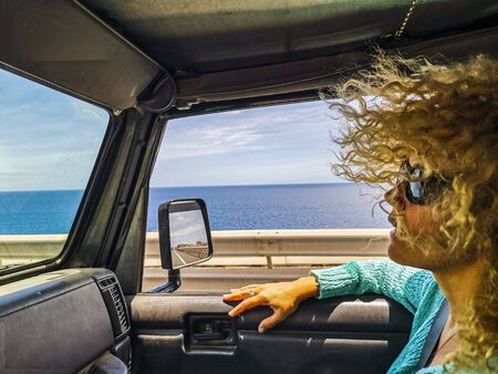 Concept of car travel with beautiful adult passenger woman enjoy the trip - ocean and blue sky view outside the window - concept of tourism and vacation transport