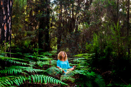 Beautiful adult lady do mindfulness exercises and yoga m editation sit down in the silence of the green nature forest - people enjoying alternative lifestyle and wood in tropical place