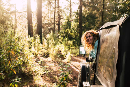 Alternative tourism people discover nature with off road car enjoying the forest and wood in the sunset sun light - cheerful happy woman outside the vehicle inside the wood