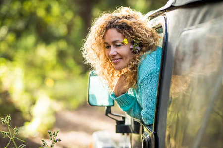 Beautiful travel concept adult woman enjoy the forest sit down inside a car and outside the window - adventure and alternaive nature love lifestyle for happy people in outdoor leisure vehicle activity Stockfoto