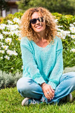 Happy and cheerful beautiful caucasian adult woman enjoy the park and smile at the camera with green natural daisy in background - spring and flower season and people happy portrait concept
