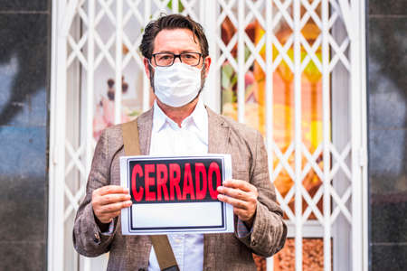 Adult professional businessman with spanish closed sign outside his store for coronavirus economy crisis emergency for lockdown at home - business recession concept with owner shop