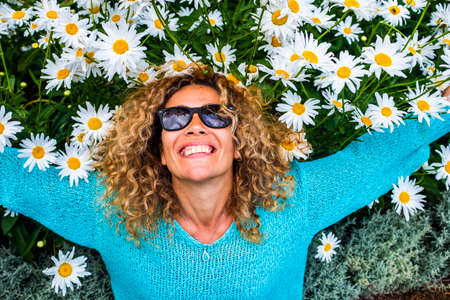 People and happiness concept lifestyle with happu and cheerful adult beautiful caucasian young woman smile with green and colored daisies background - leisure activity and park outdoor