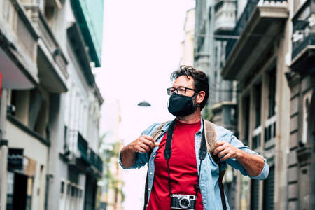 Tourist and tourism during coronavirus epidemic emergency - standing man with camera gear and backpack enjoy the street of the city - vacation and outdoor leisure activity in lockdown covid-19 time
