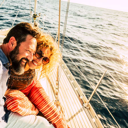 Happy and cheerful caucasian couple enjoy the sail boat trip together - sunny summer holiday vacation day for beautiful adult people enjoying yacht and ocean outdoor travel Stockfoto