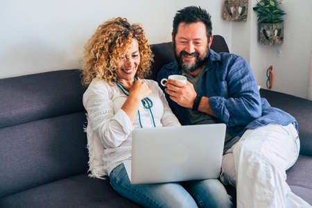 Happy adult aged couple caucasian people at home with personal laptop computer and internet connection - together in indoor leisure activity with technology sitting on the sofa and smiling
