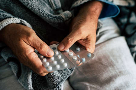 close up of hands of senior man taking or choosing a pillow to cure his fever and to be healthy and not sick - pensioner and retired alone at home - pharmacy usually life for old people
