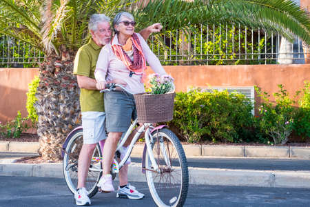 Old senior people couple enjoy retired lifestyle riding together the same colored bike in outdoor leisure activity - smile and love forever - active mature man and woman having fun