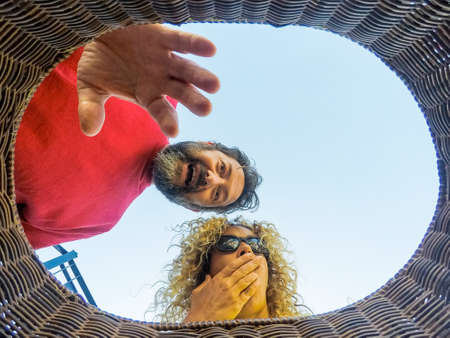 Adult caucasian couple look inside a bucket and do surprised expression - indoor inside wide view - surprise concept with blue sky in background and man and woman Stockfoto