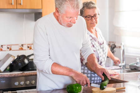 Beautiful senior adult caucasian people couple at home working together in the kitchen - equal rights concept with man and woman cooking - happy real life after retiremen - mature lifestyle