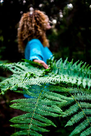 Concept of environment and save the planet earth with close up of tropical green leaf and woman in background - nature and outdoor forest care for people loves the outdoors
