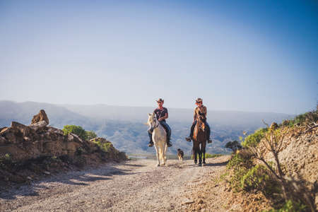 outdoor cowboy life couple ride horses at the mountain enjoying excursion in the nature together - alternative vacation travel lifestyle for alternative people