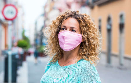 Portrait of beautiful caucasian adult woman wear protection mask during coronavirus covid-19 health emergency - city and street with nobody in backgorund - concept of lockdown and contagion Stockfoto