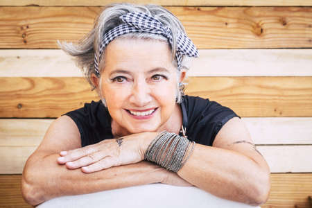 Portrait of cheerful caucasian senior happy woman with wood background - alternative and young old female smile and enjoy - tatooed skin for diversity concept and age - youthful lifestyle