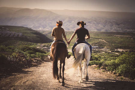 Romantic couple wide horses together holding hands with love and romance in outdoor leisure lifestyle alternative activity - viewed from back young people with aninmals Stockfoto