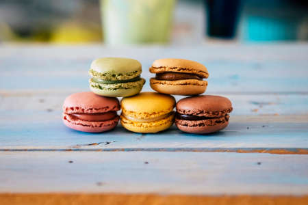 Close up of tasty bakery macarones on a blue woden rustic table - sweet cakes made from bakery chef with cream and chocolate flavors