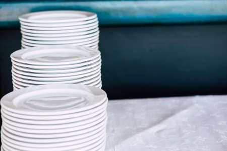 Pile of white clean dishes on a table - close up of kitchen stuffs for catering or restaurant business concept
