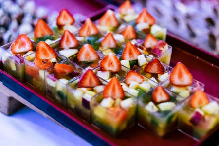 Close up of healthy and fresh seasonal little portion. cakes with strawberry and other fruits for wedding or party catering job - colorful food background image Stockfoto