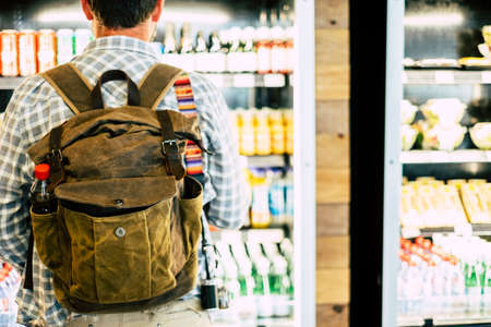 Travel man viewed from back in front of an automatic drink store choosing snacks or beverage before leave or start the business or vacation trip - view from rear at the backpack